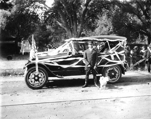 Historic photo of Wilbur Julius & Toy Poodle Beside Parade Car