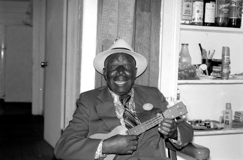 "Photo of William ""Washboard Bill"" Cooke poses with his ukulele"