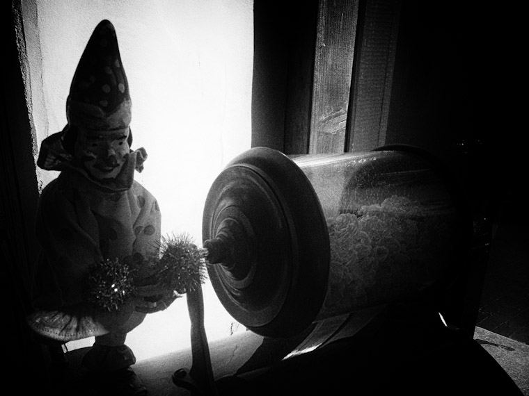 Creepy picture of antique clown rotating popcorn in black and white