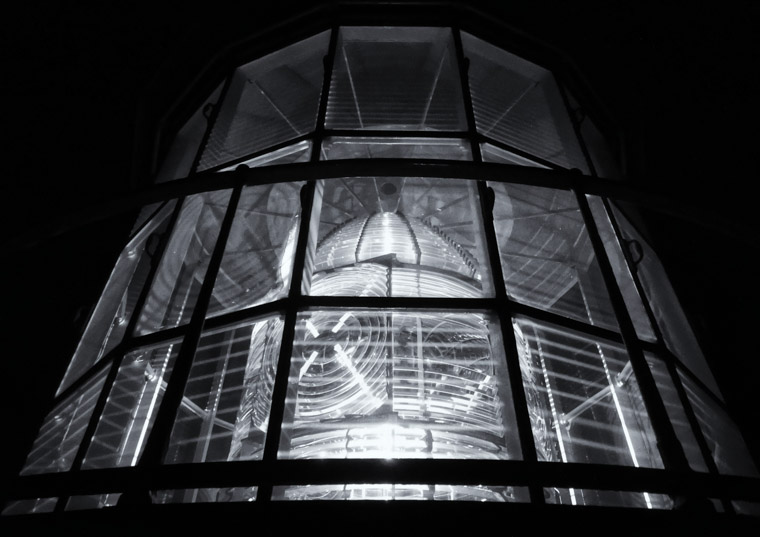 Night view of lighthouse lens up close at night