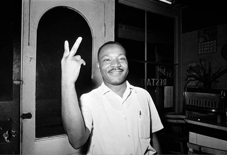 Martin Luther King Jr flashes a peace sign in st augustine after learning civil rights act passed