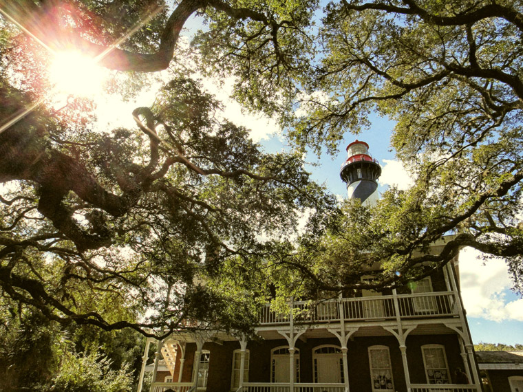 Lighthouse and sunshine with live oaks