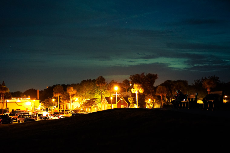 People sitting on bench at night at fort