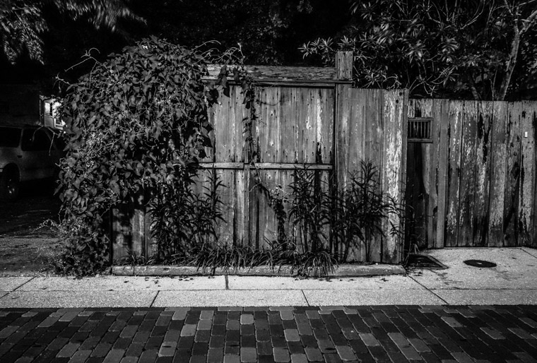 Wooden fence and street at night