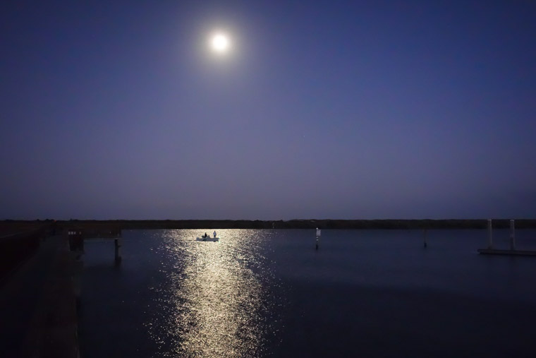 Fishing from boat at night by dock