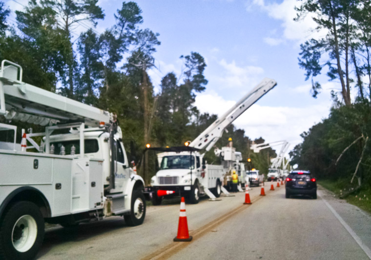 Electric company bucket trucks working on power lines